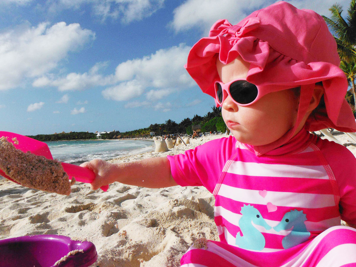 Baby playing in sand at on of the Best baby friendly all inclusive resorts