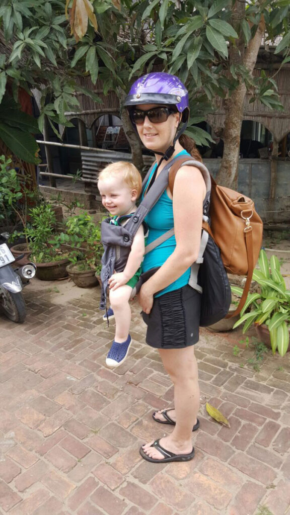 mother carrying baby and portable travel high chair