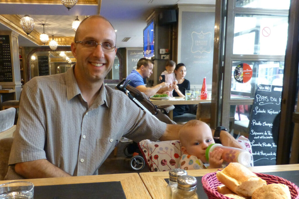 father and baby eating in restaurant with baby in portable fabric travel high chair