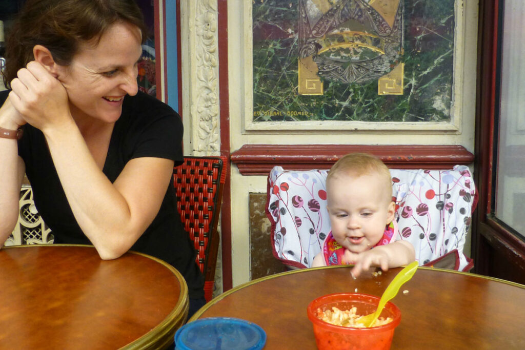 mother and baby eating in restaurant with baby in my little seat portable fabric high chair