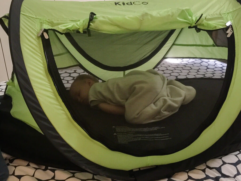 Toddler sleeping in KidCo PeaPod Plus portable travel bed