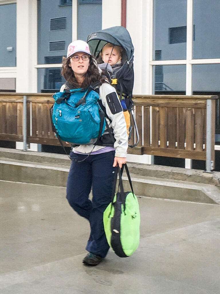 Mother carrying folded kidco peapod plus portable travel bed