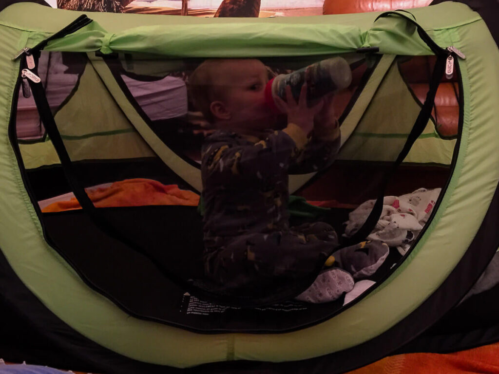 toddler sitting up in KidCo PeaPod Plus portable bed for toddlers