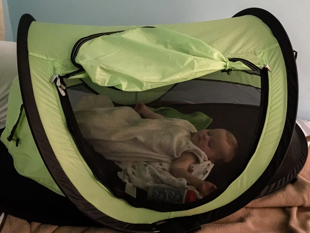 Toddler sleeping in KidCo PeaPod Plus travel bed