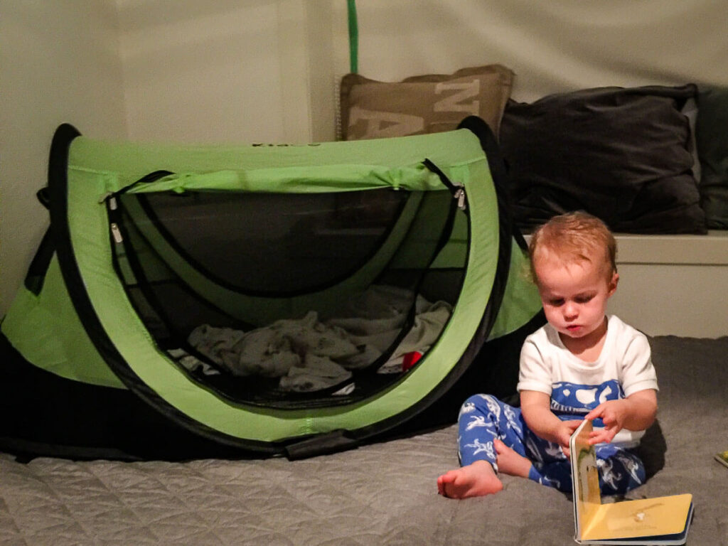 Toddler sitting beside kidco peapod tent