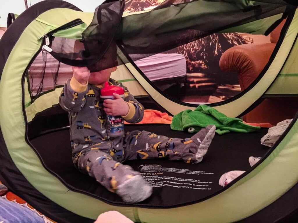 Toddler sitting in KidCo PeaPod Plus - Review of toddler travel bed