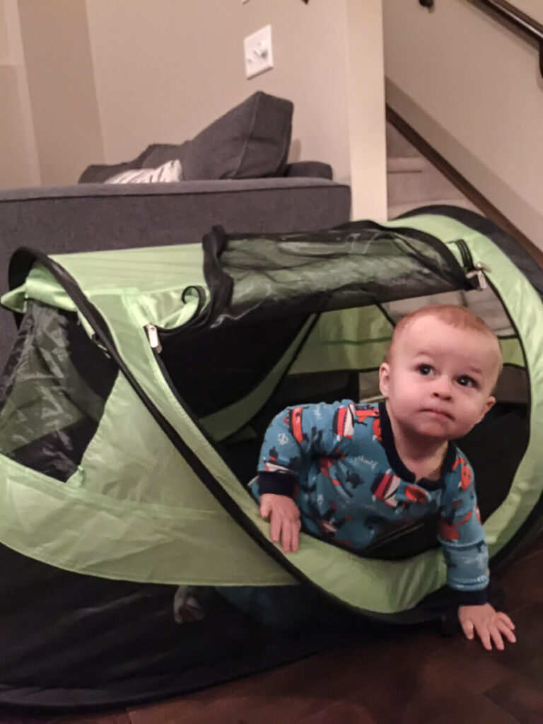 toddler peaking out of KidCo PeaPod Plus