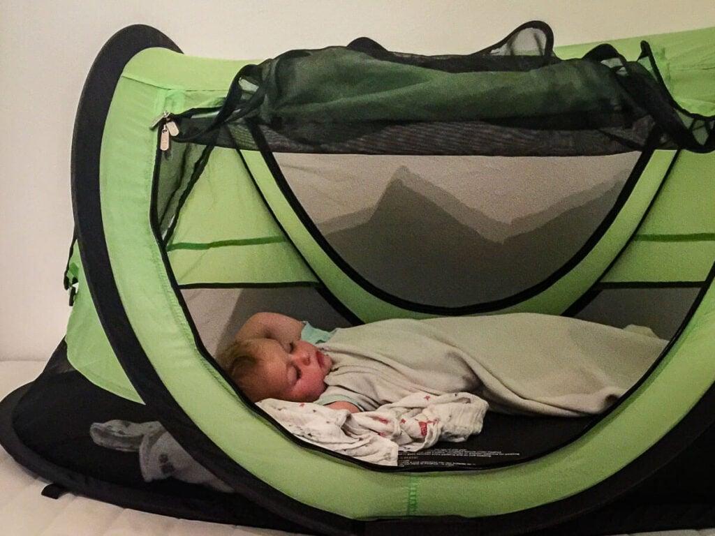 Toddler sleeping in KidCo PeaPod Plus travel tent