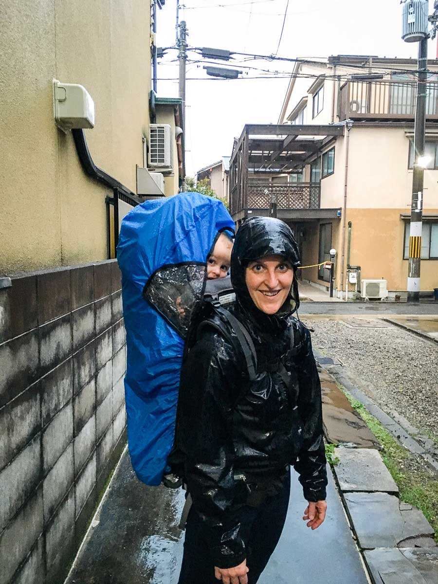 hiking in the rain with baby using backpack carrier with rain cover