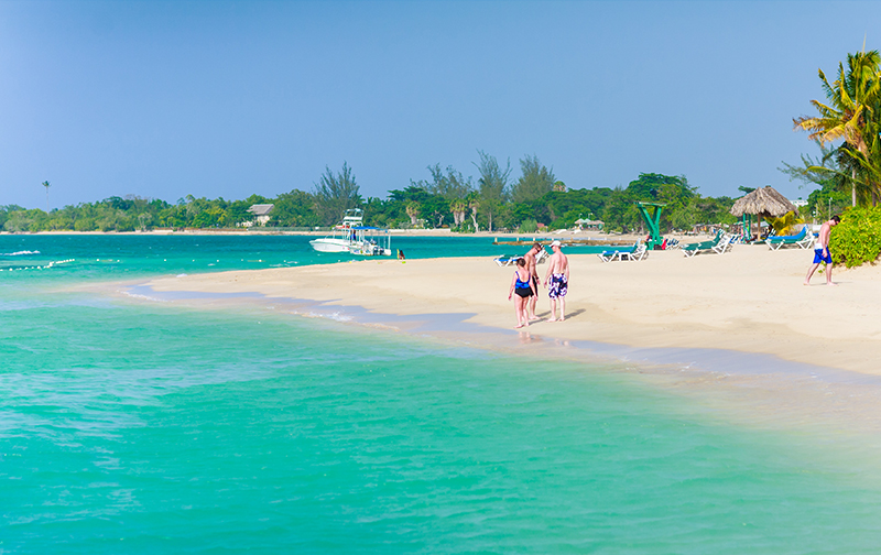 Guests walk by the turquoise Caribbean Sea in Jamaica