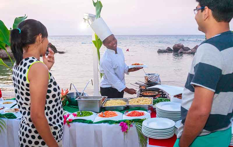 A chef preparing food by the sea at Franklyn D. Resort