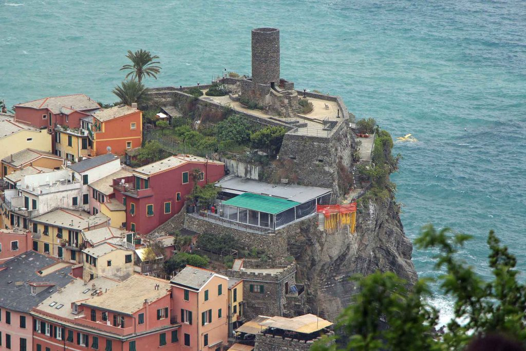 An aerial view of the Belforte Tower in Vernazza, Cinque Terre, Italy as seen from a hiking trail above town
