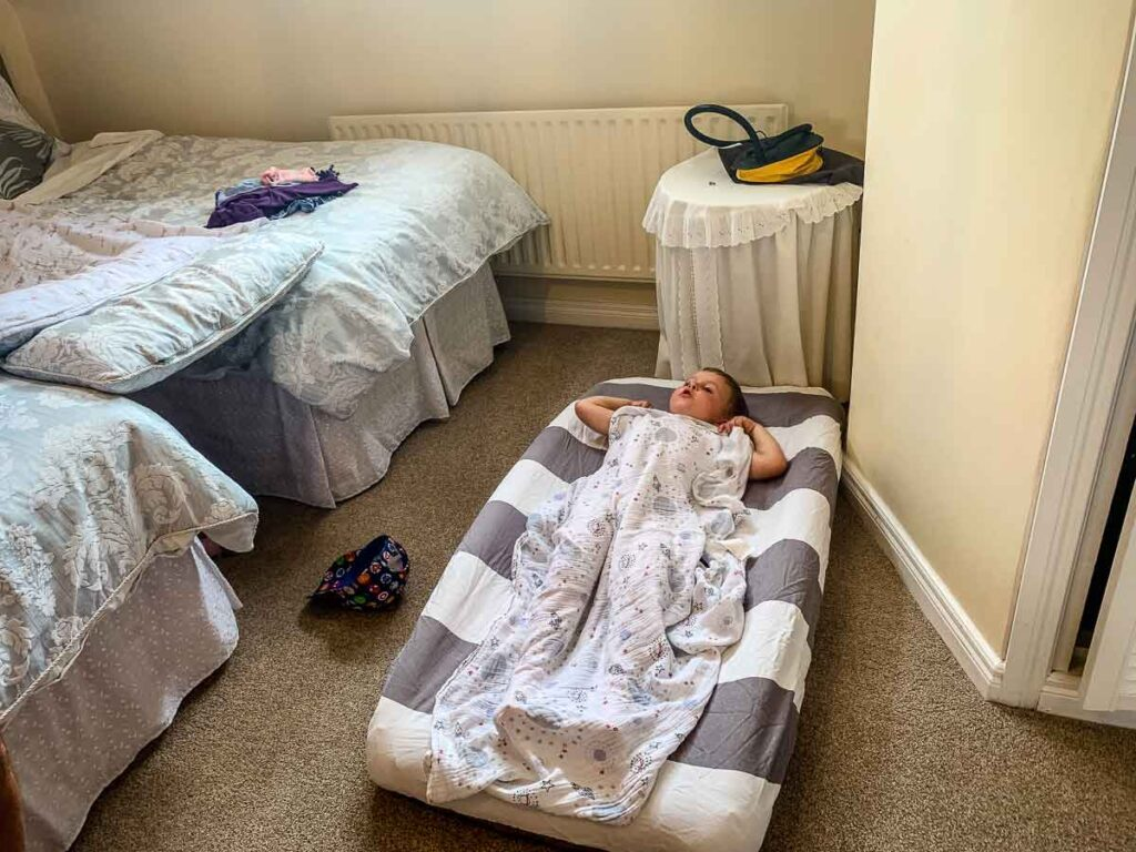 Toddler on inflatable toddler travel bed in hotel room