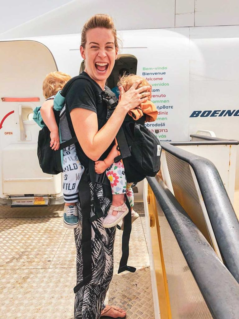 mom using twin baby carrier for travel