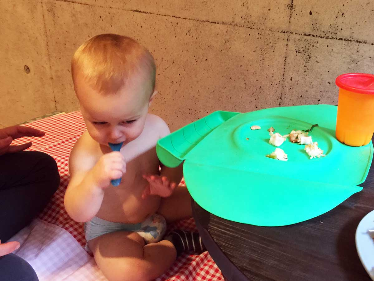 baby eating from silicone place mat - travelling with a baby essentials