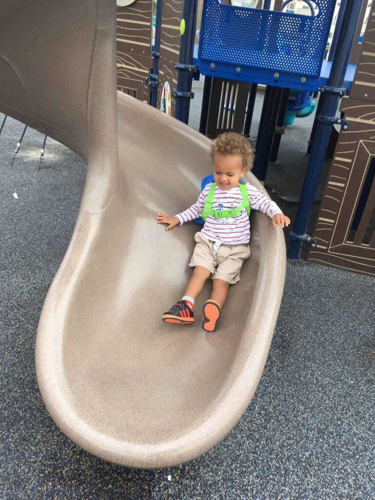 Image of toddler on slide at playground in Huntington Beach