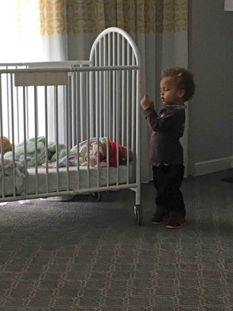 image of toddler near crib in hotel room in Huntington Beach