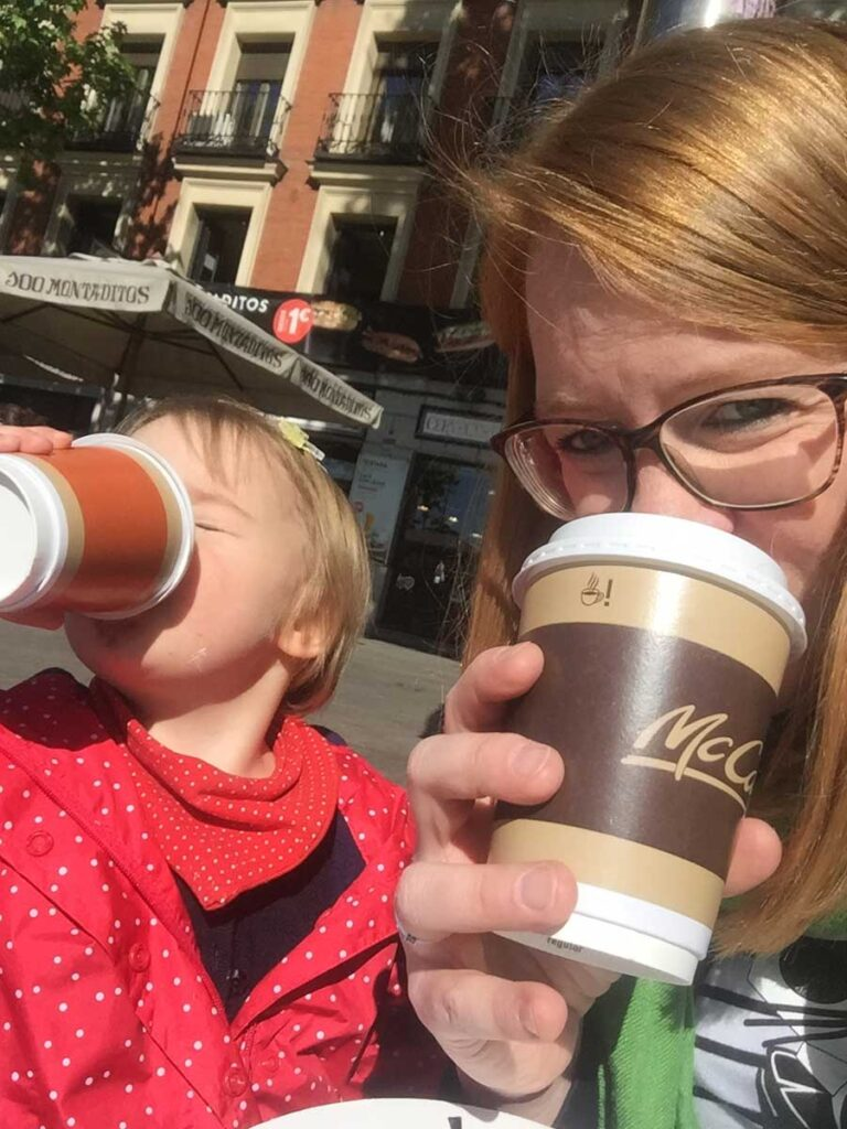 mom drinking coffee in Madrid with toddler