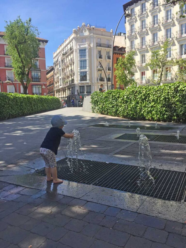 toddler playing in fountain in Madrid