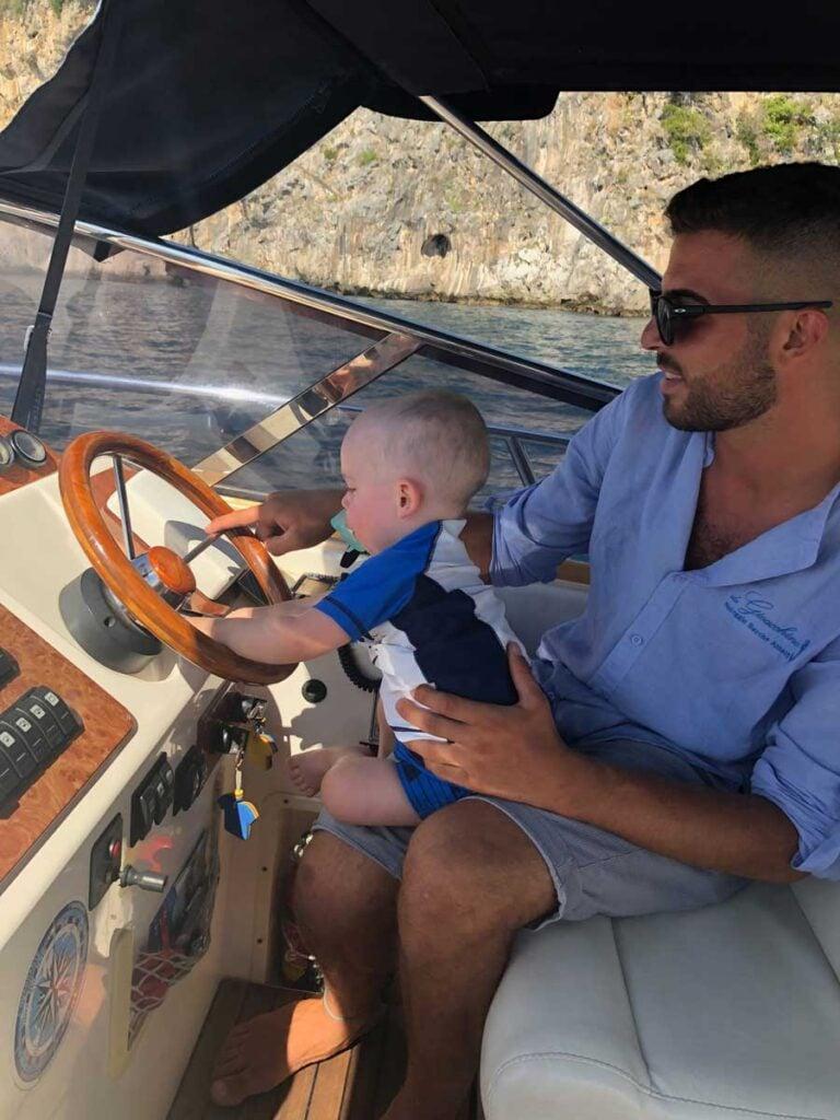 image of man holding baby on boat Amalfi Coast