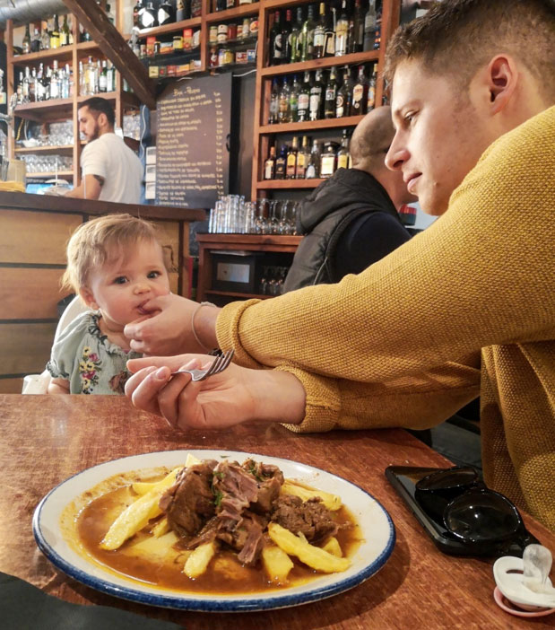 image of father and baby eating in restaurant in seville spain