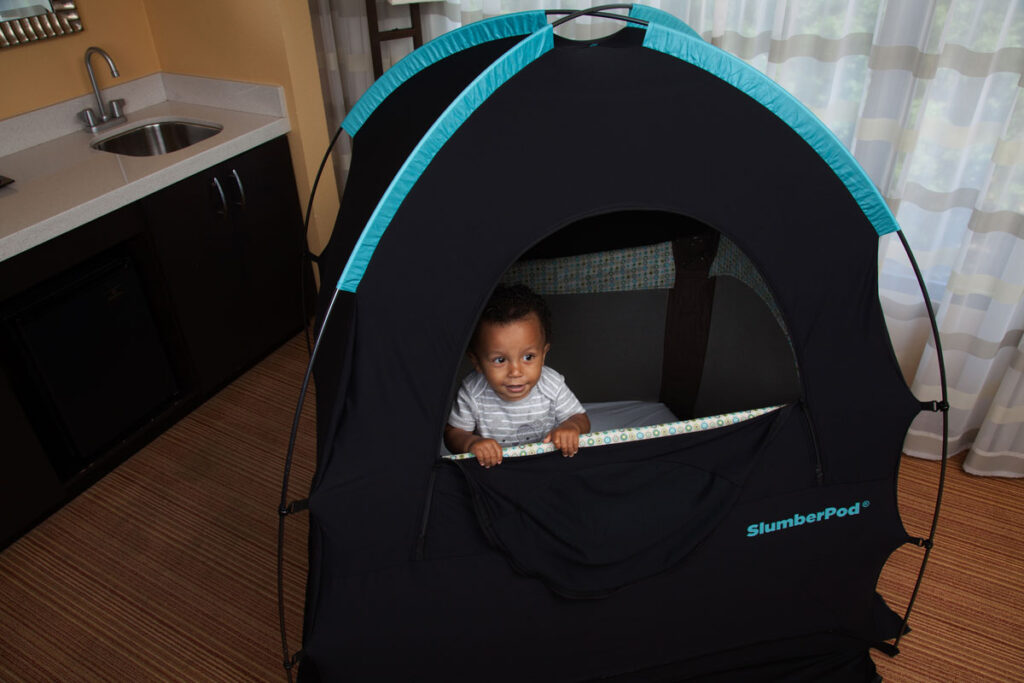 image of toddler boy in pack n play in Slumberpod Privacy Pod
