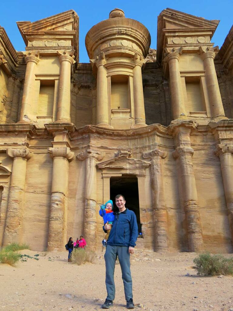 Image of man holding baby in front of Monastery in Petra