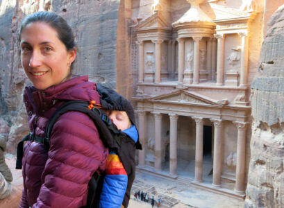 image of woman with baby in carrier on her back at Petra with the Treasury in background