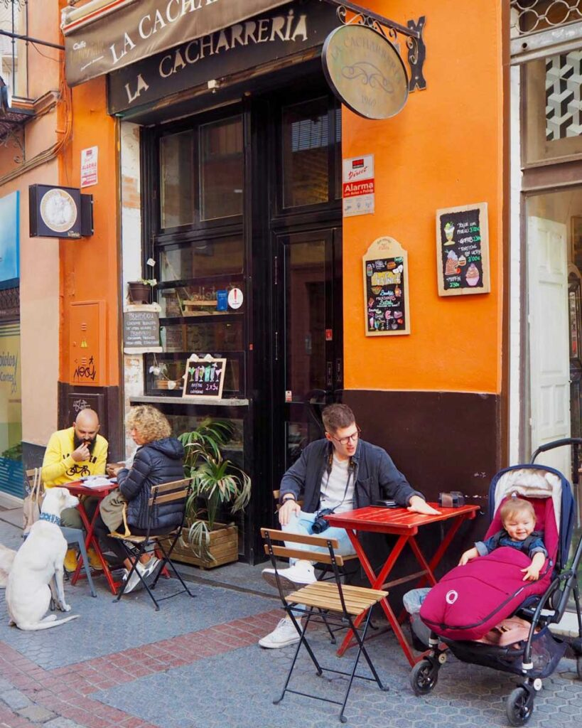 image of man at restaurant in Seville with baby in stroller at table