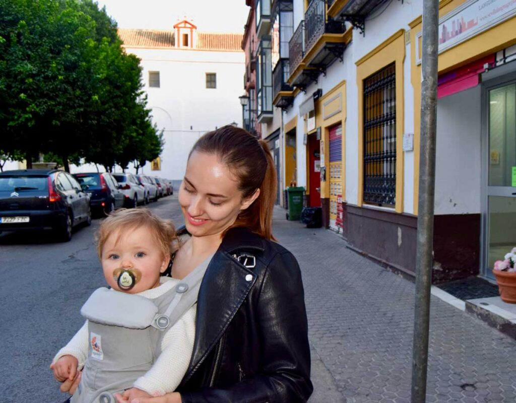 image of woman traveling with a baby in baby carrier