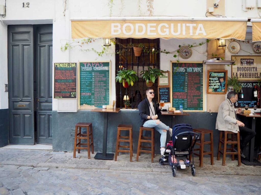 Image of man at outdoor table eating Tapas in Seville Spain with baby in Stroller next to him