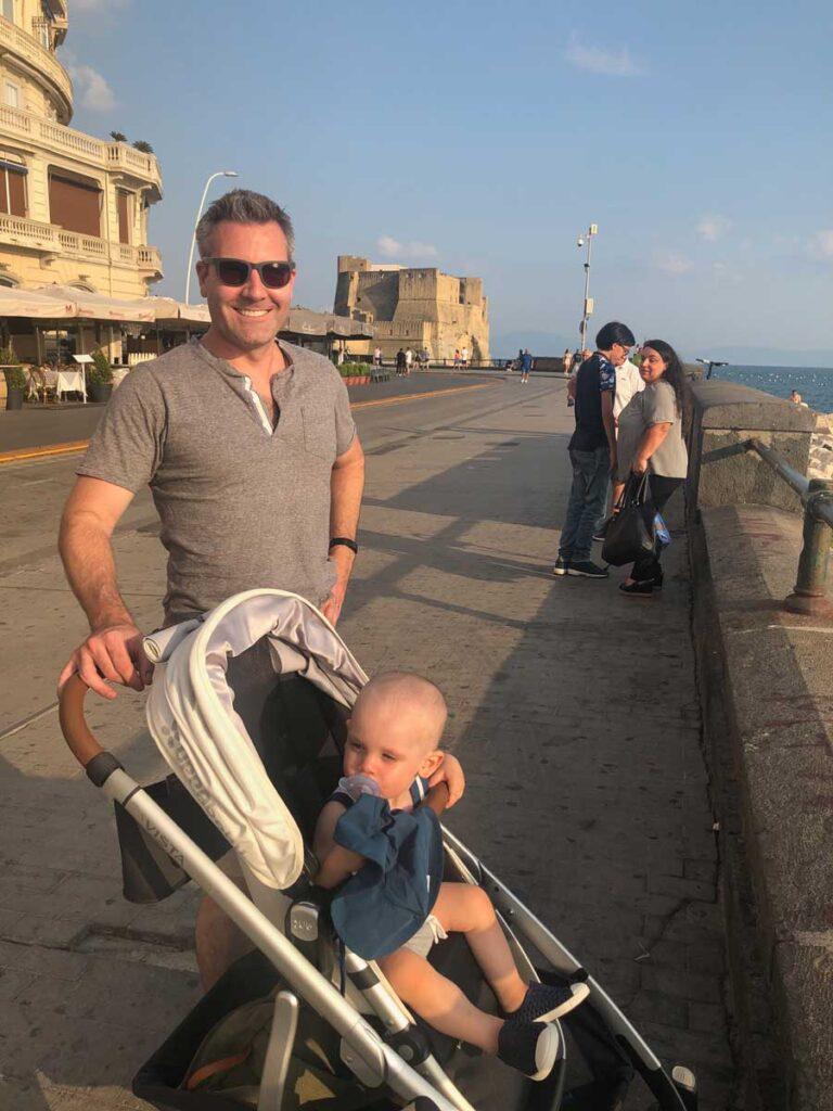 image of man pushing toddler in stroller in Italy