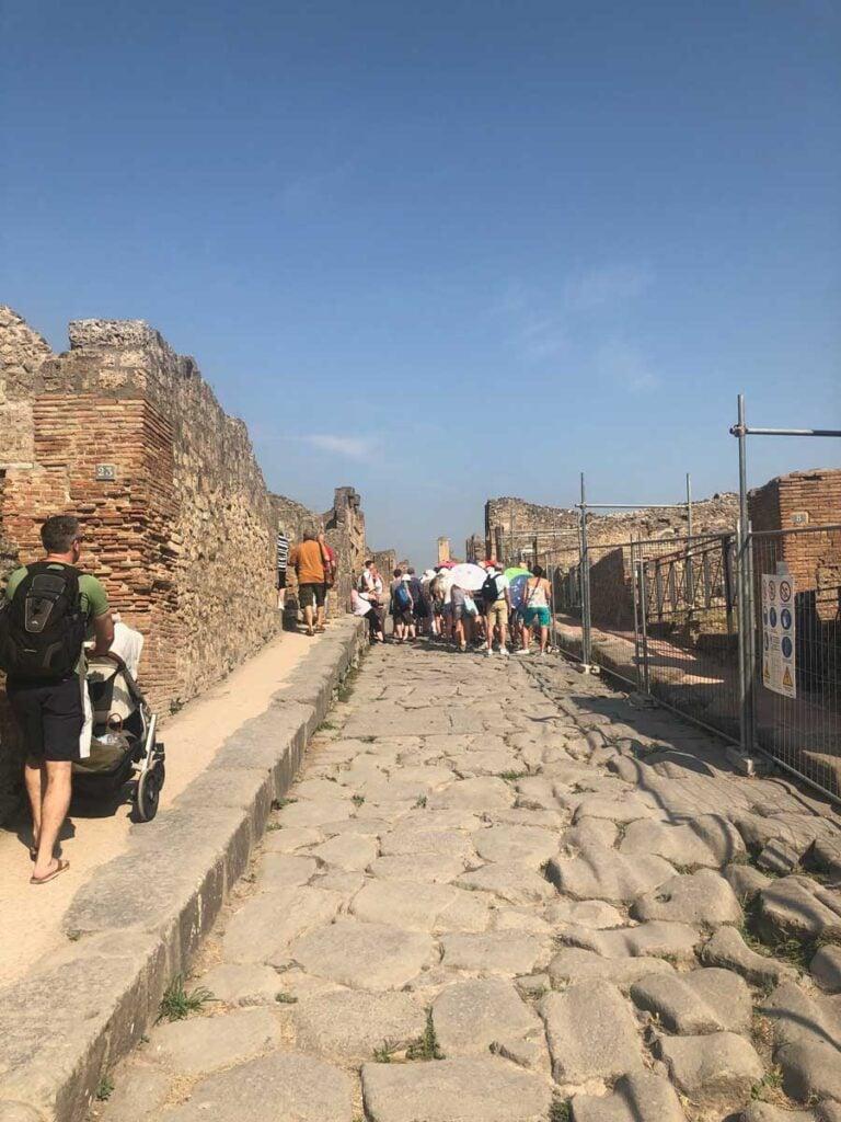 image of man pushing stroller at Pompeii