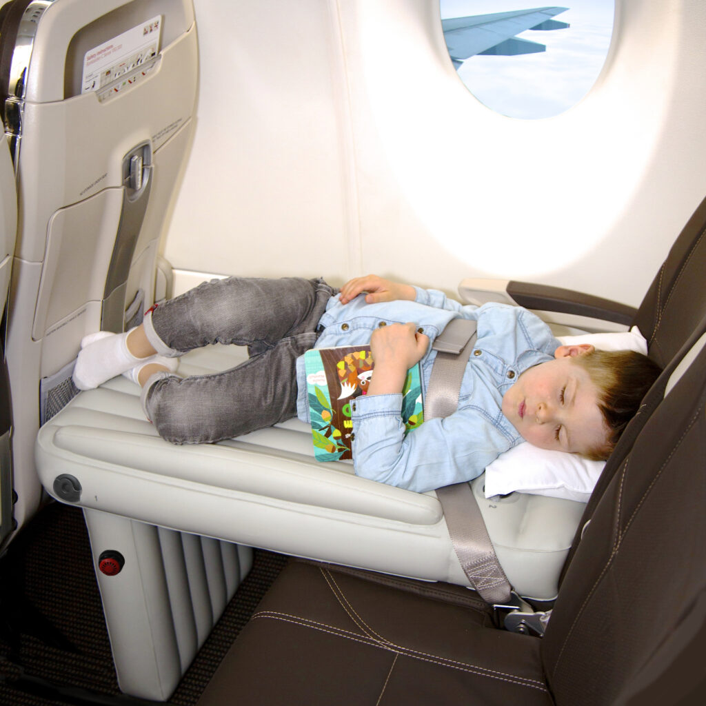 image of toddler holding book sleeping on plane on airplane travel bed for kids
