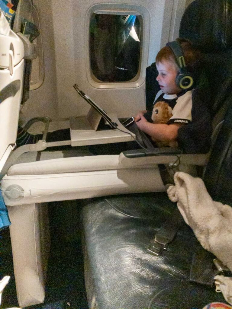 image of boy on travel bed for toddler on plane