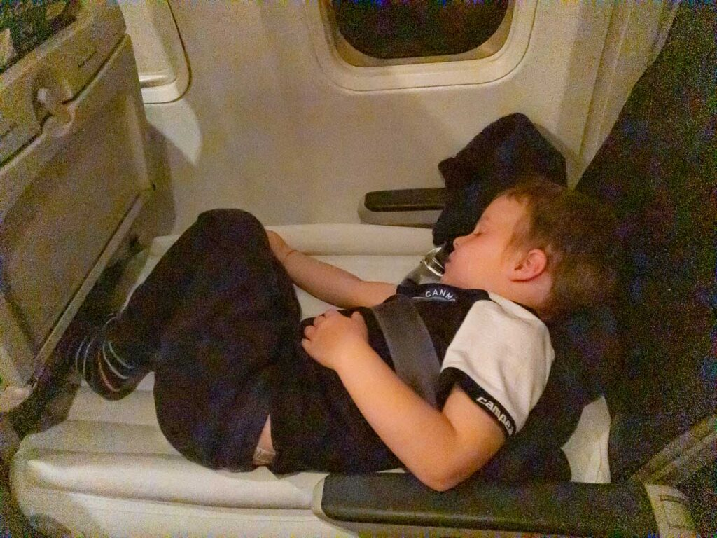 image of getting a toddler to sleep on a flight with a toddler bed for plane