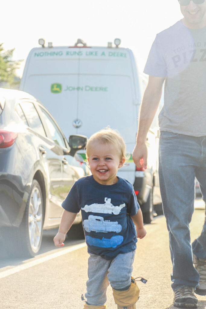 image of toddler walking beside cars on road with father behind him