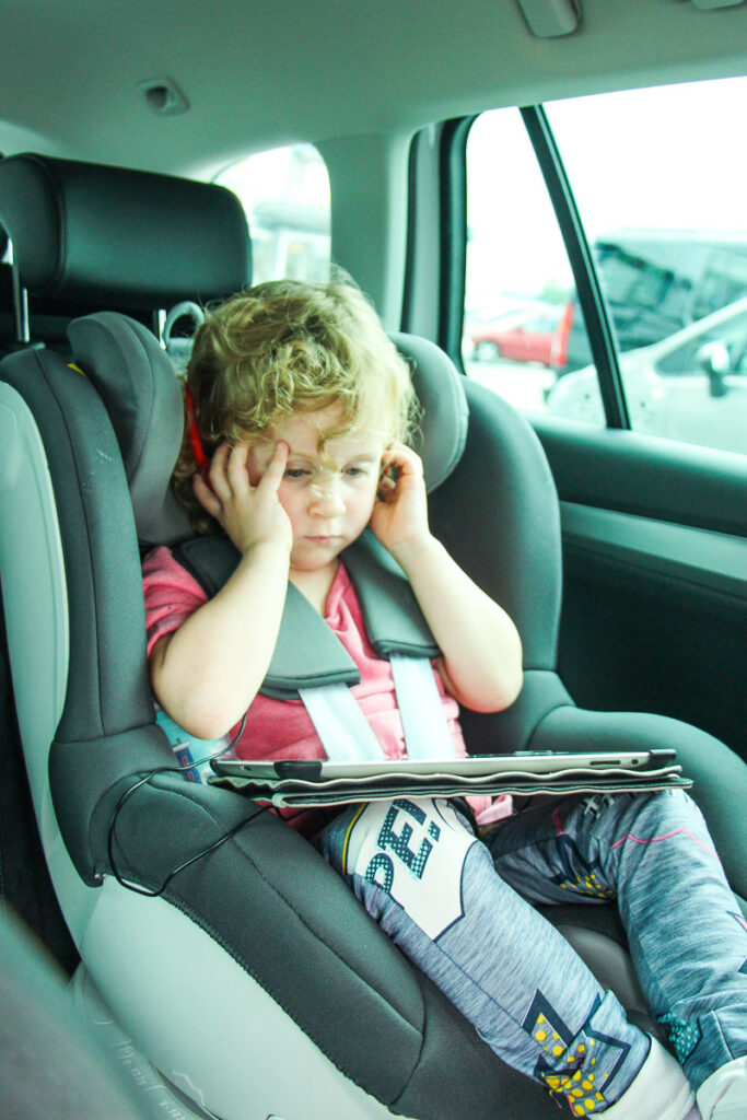 image of toddler on road trip with ipad and headphones