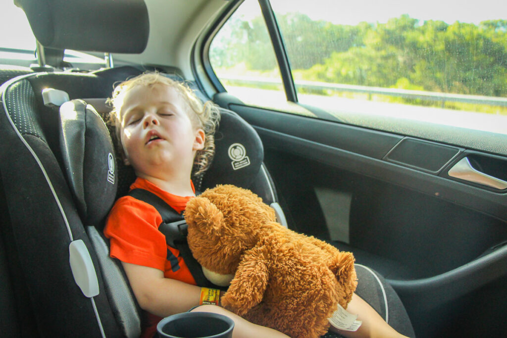 image of road trip with toddler sleeping in car seat