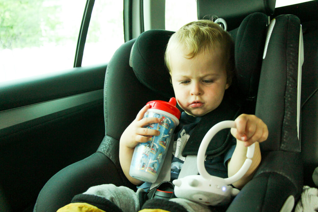 image of toddler in car seat with a sippy cup