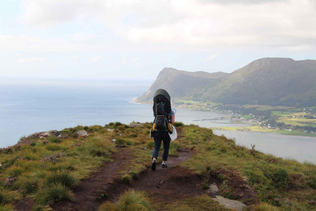 A mom hiking in Norway uses a Deuter Kid Comfort 3 to carry her toddler to a viewpoint
