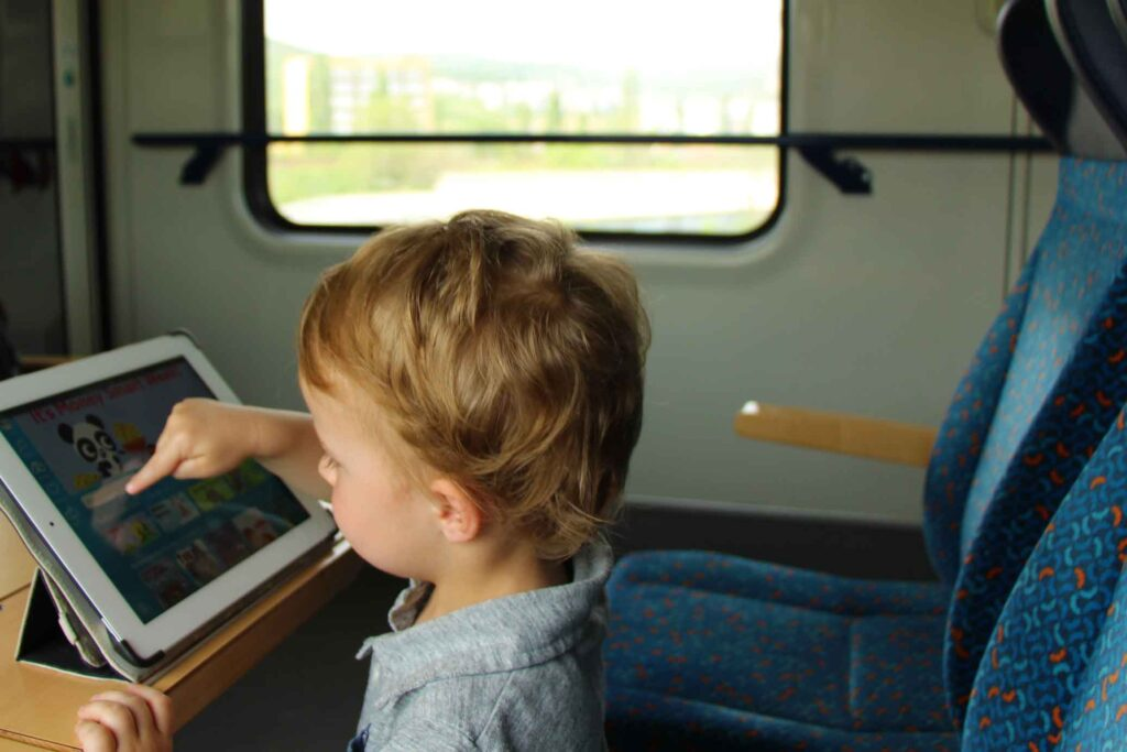 A toddler uses the Epic! digital library reading app on a train