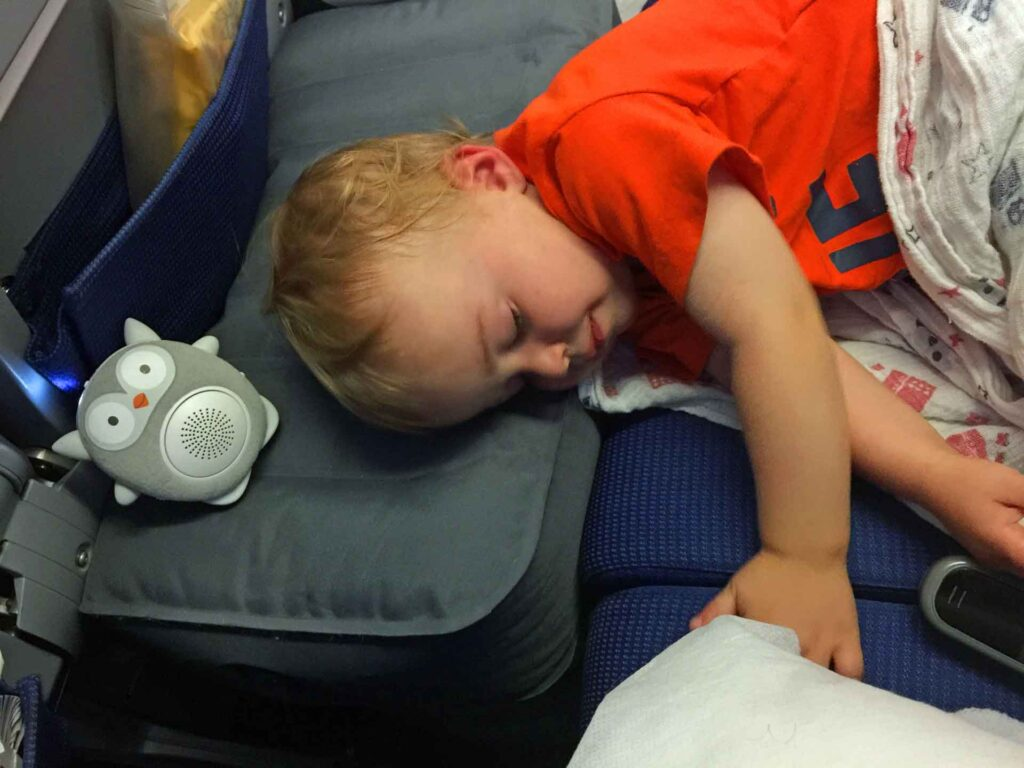 A toddler sleeps on an airplane using a Fly Tot inflatable airplane cushion