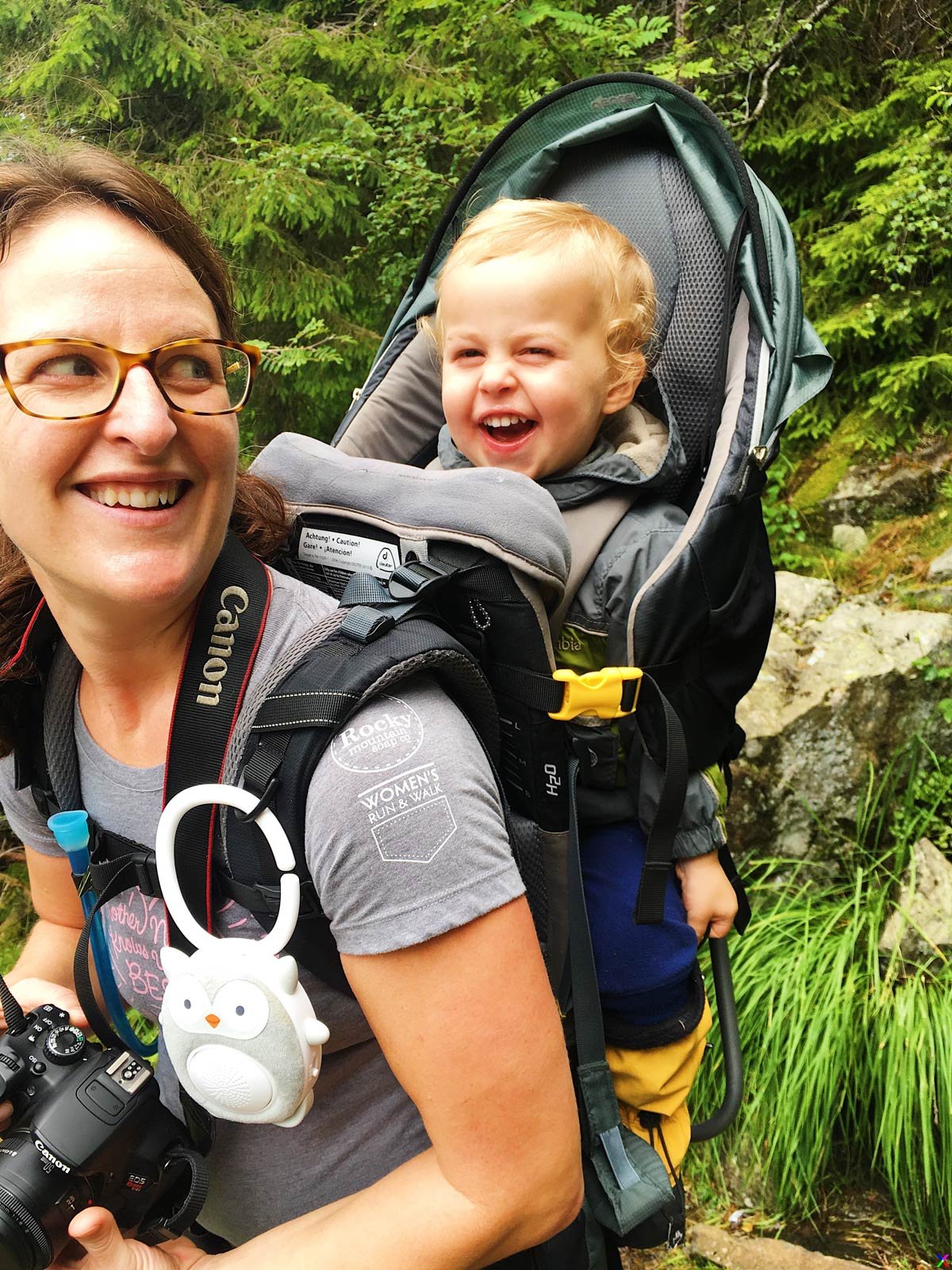 A toddler laughs while hiking in a Deuter Kid Comfort 3 backpack carrier