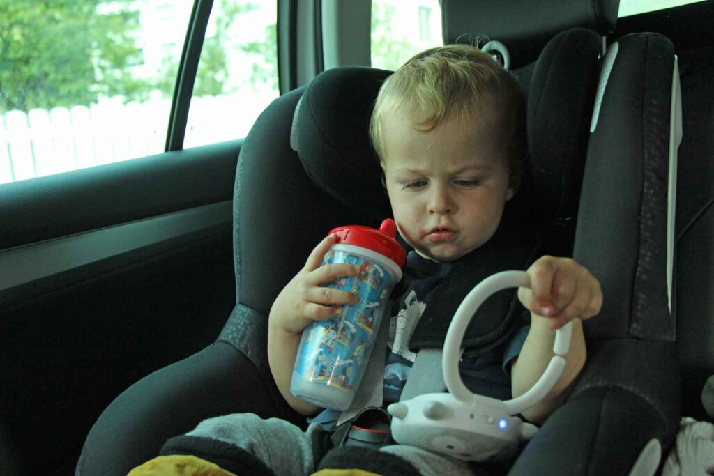 A toddler in a car seat holds a toddler travel cup and a white noise machine