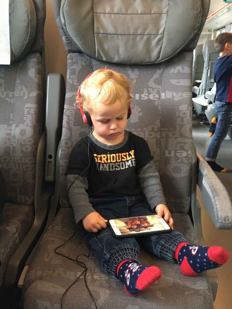 A toddler uses headphones to watch a show on an iPad during a flight