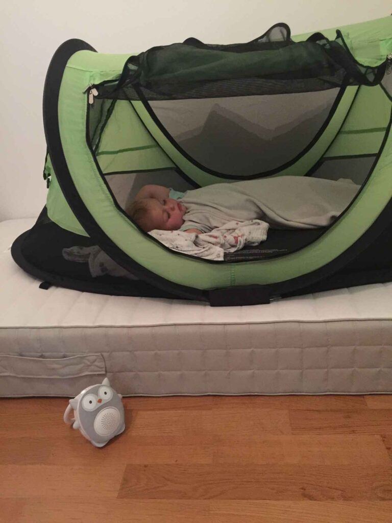 A toddler sleeps in a PeaPod Plus travel bed while using a SoundBub white noise machine