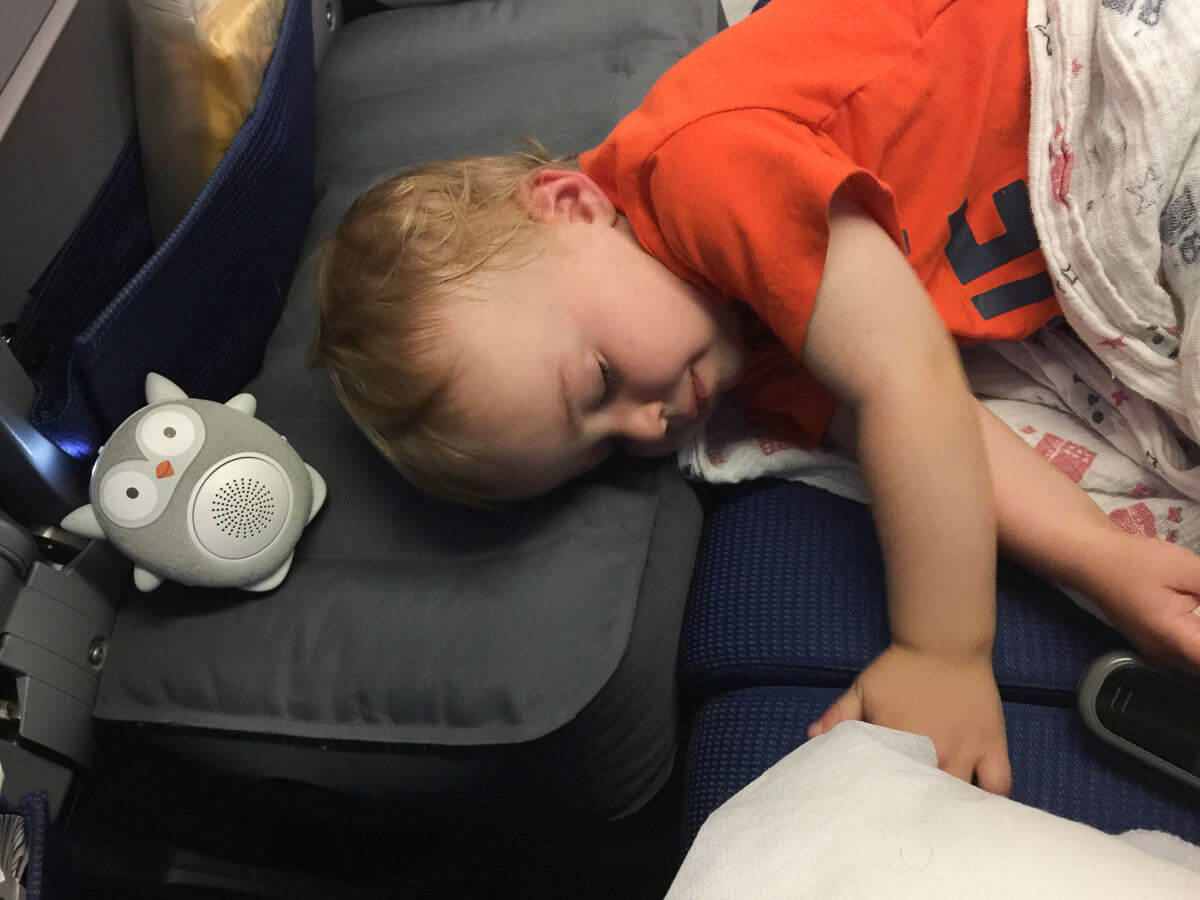 image of toddler sleeping on inflatable airplane cushion on airplane