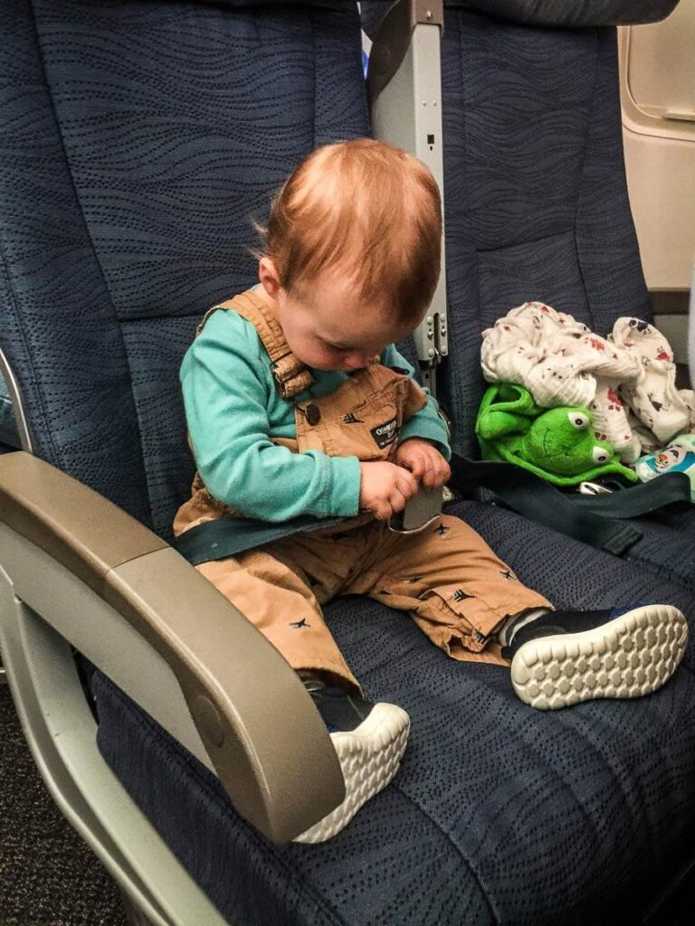 image of toddler on airplane playing with seatbelt