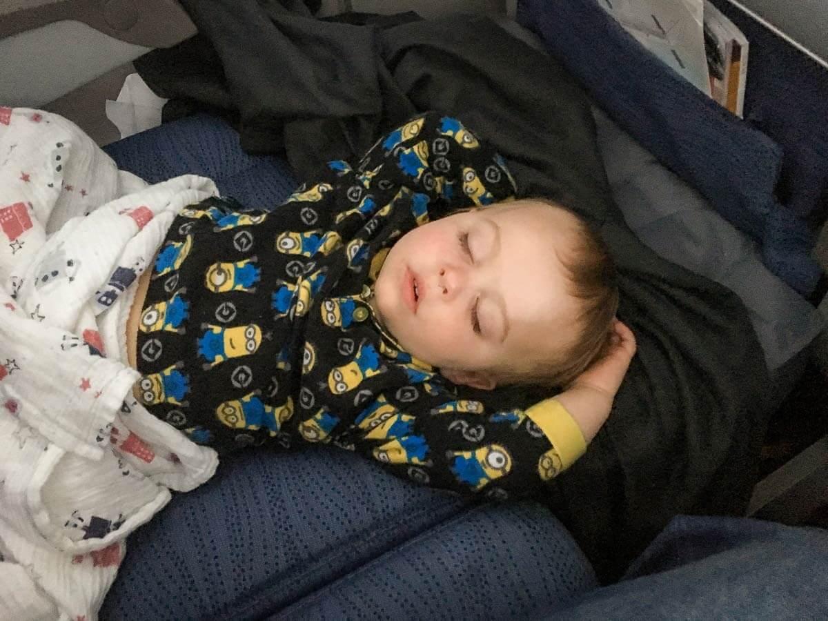 image of toddler sleeping on plane